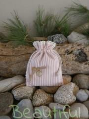Μοντέρνα μπομπονιέρα. Μπομπονιέρα βάπτισης κορίτσι πουγκί, υφασμάτινο ριγέ ροζ με μεταλλικό ματάκι και κορδόνι λινάτσα χειροποίητο.